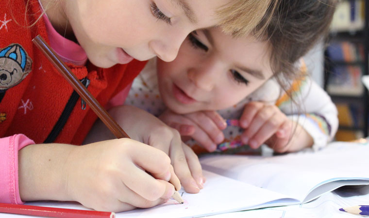 Two little girls draw a picture